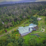 aerial property view of the main farmhouse and the eco-cottage & a few of the gardens at papalani