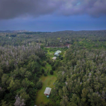 aerial photo taken from the top of 3 of the acres (at hale la) looking down toward the ocean on a cloudy day.
