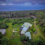 aerial of the bottom couple acres with ohana & farmhouse and carports.  on the left of the photo is the roof of the eco-cottage and agricultural water tank.